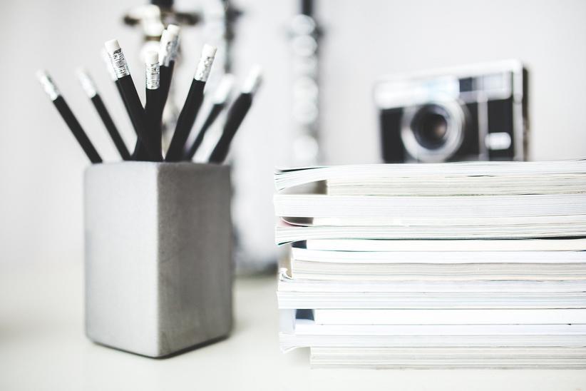 Skrivebord med blyanter, kamera og en bokstabel